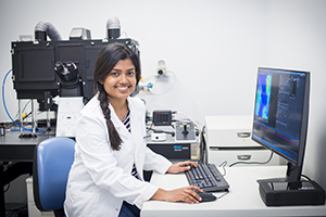 Photo of a female researcher at a microscope