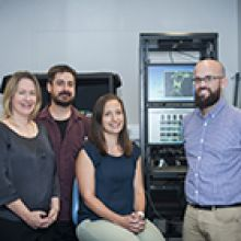 Four researchers in an imaging facility room